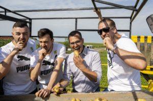 Jannnik Kohlbacher, Patrick Groetzki, Hartmut Magin, und Oliver Roggisch, auf der Rodemaschine tun so, als würden sie in die rohen Kartoffen beißen